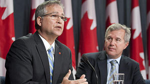 Minister of State for Science and Technology Gary Goodyear, seen accepting a report on innovation from Tom Jenkins, right, in October, says changes are coming to the way Canada funds research and development.